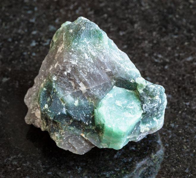 raw-crystal-of-beryl-gemstone-in-rock-on-black