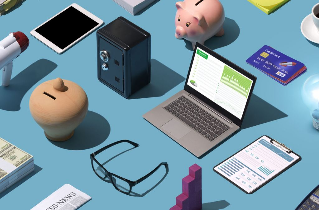 Business isometric desktop with laptop, lit bulb and assorted financial items